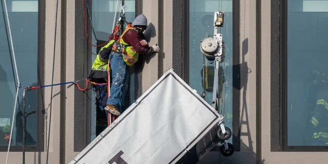 A worker stands on the end of a dangling scaffold as he waits to be rescued following an explosion at Baltimore Gas and Electric's offices, on Wednesday. Twenty-one of the victims were brought to area hospitals following the explosion with a partial roof collapse. The city's fire department tweeted that at least nine of the victims were in critical condition, while another was in serious condition. (Jerry Jackson/The Baltimore Sun via AP)