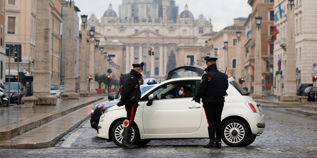 Italian Carabinieri officers check vehicles in front of St. Peter's Basilica at the Vatican, Thursday, Dec. 24, 2020. Italians are easing into a holiday season full of restrictions, and already are barred from traveling to other regions except for valid reasons like work or health. Starting Christmas eve, travel beyond city or town borders also will be blocked, with some allowance for very limited personal visits in the same region. (Cecilia Fabiano/LaPresse via AP)