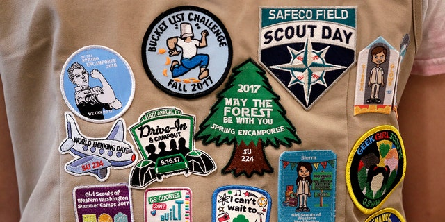 "LÊER - In this June 18, 2018, lêerfoto, patches cover the back of a Girl Scout's vest at a demonstration of some of their activities in Seattle. Girl Scouts of the United States of America claim the century-old organization is in a ""highly damaging"" recruitment war with Boy Scouts of America after the group opened its core services to girls, leading to marketplace confusion and some girls unwittingly joining the Boy Scouts. (AP Photo/Elaine Thompson, lêer)"