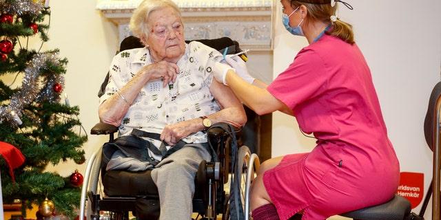 Nurse Ann-Louise Broberg injects a COVID-19 vaccine to nursing home resident Gun-Britt Johnsson in Mjolby, Sweden, Sunday, Dec. 27, 2020. Gun-Britt was the first in Sweden to receive the vaccine. (Stefan Jerrevang/TT News Agency via AP)