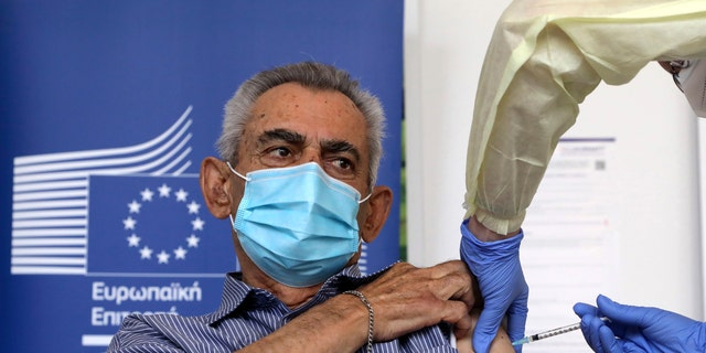 Andreas Raounas, 84, the first patient in Island receives from a nurse the vaccine of Pfizer BioNtech against the COVID-19, at a care home in Nicosia, Cyprus, Sunday, Dec. 27, 2020. Cyprus started today the vaccination program against COVID-19. (Katia Christodoulou/Pool Photo via AP)