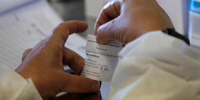 A nurse prepares a dose of the Pfizer-BioNTech COVID-19 vaccine at the Santa Maria Hospital in Lisbon on Sunday, December 27, 2020. Portugal began its vaccination program on Sunday, and medical staff at reference hospitals across the country received the first shot.  (AP Photo/Armando Franca)