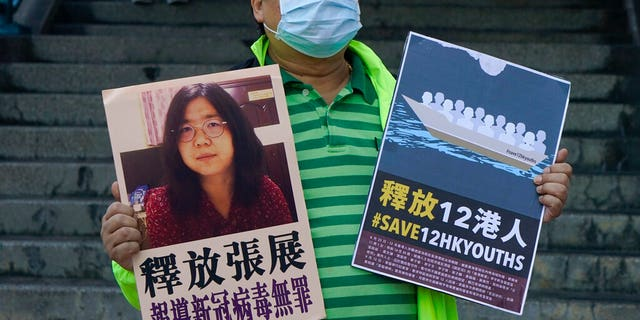 A pro-democracy activist holds placards with the picture of Chinese citizen journalist Zhang Zhan outside the Chinese central government's liaison office, in Hong Kong. (AP Photo/Kin Cheung)