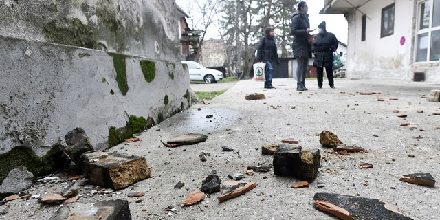Residents inspect damage caused by an earthquake in Sisak, Croatia, Maandag, Des. 28, 2020. A moderate earthquake has hit central Croatia near its capital of Zagreb, triggering panic and some damage south of the city. There were no immediate reports of injuries. (AP-foto)