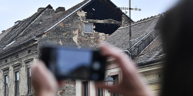 A resident takes a photograph of the damage caused by an earthquake in Sisak, Croatia, Maandag, Des. 28, 2020. A moderate earthquake has hit central Croatia near its capital of Zagreb, triggering panic and some damage south of the city. There were no immediate reports of injuries. (AP-foto)