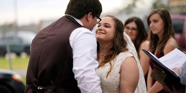 Emily and Taylor Pascale kiss after exchanging vows at their wedding outside the home of Taylor's parents in Grand Lake, Louisiana, which was heavily damaged from Hurricanes Laura and Delta. (AP Photo/Gerald Herbert)