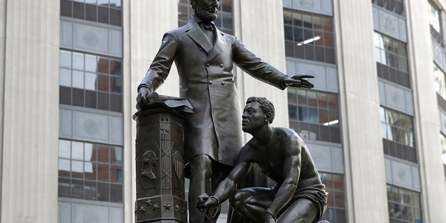 FILE - In this June 25, 2020, 档案照片, a statue that depicts a freed slave kneeling at President Abraham Lincoln's feet rests on a pedestal in Boston. 星期二, 十二月. 29, the statue that drew objections amid a national reckoning with racial injustice was removed from its perch. (AP Photo/Steven 文件e, File)
