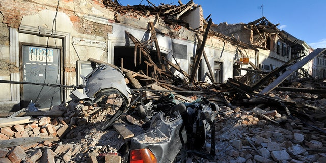 A view of remains of a car covered by debris and buildings damaged in an earthquake in Petrinja, Croazia, martedì, Dic. 29, 2020. A strong earthquake has hit central Croatia and caused major damage and at least one death and 20 injuries in a town southeast of the capital Zagreb. (Foto AP)