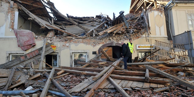 People walk through the rubble from buildings damaged in an earthquake in Petrinja, Croatia, Dinsdag, Des. 29, 2020. A strong earthquake has hit central Croatia and caused major damage and at least one death and some 20 injuries in the town southeast of the capital Zagreb. (AP-foto)