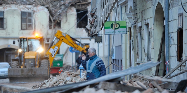 A man stands amidst the rubble from buildings damaged in an earthquake in Petrinja, Croazia, martedì, Dic. 29, 2020. A strong earthquake has hit central Croatia and caused major damage and at least one death and some 20 injuries in the town southeast of the capital Zagreb. (Foto AP)