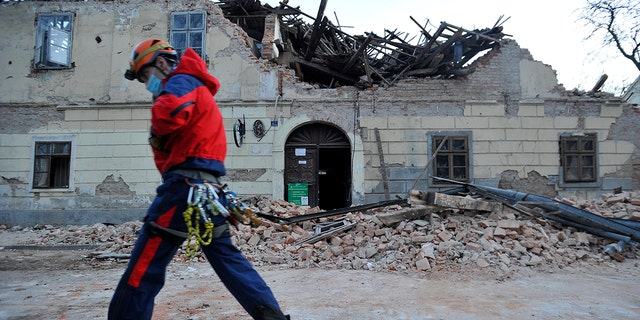 A rescuer walks past a building damaged in an earthquake in Petrinja, Croatia, Dinsdag, Des. 29, 2020. A strong earthquake has hit central Croatia and caused major damage and at least one death and some 20 injuries in the town southeast of the capital Zagreb. (AP-foto)