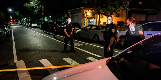 이번 7 월 18, 2020, 파일 사진, police officers respond to a crime scene were two individuals were shot on Atlantic Avenue in the Brooklyn borough of New York. Heralded as the safest big city in America in recent years, New York City is closing out its bloodiest year in nearly a decade. (AP Photo/John Minchillo, 파일)
