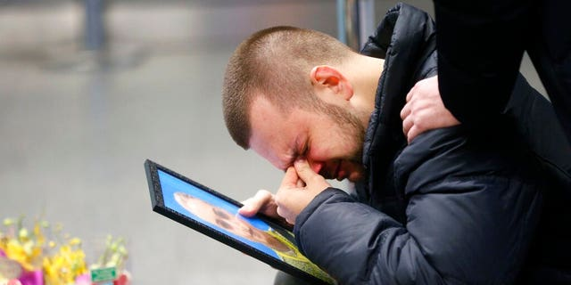 LÊER: The partner of Julia Sologub, a member of the flight crew of the Ukrainian 737-800 plane that crashed on the outskirts of Tehran, reacts as he holds a portrait of her at a memorial inside Borispil international airport outside in Kyiv, Oekraïne.