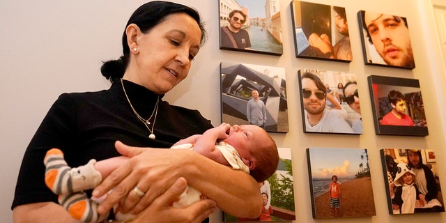 Mercedes Lemp poses for The Associated Press by holding her 2-day-old grandson near portraits of the newborn's father, Duncan Lemp, 금요일, 10 월. 16, 2020, in Frederick, Md. The Lemp's are dealing with the death of their Duncan Lemp, who was shot at their home in Potomac, Md., during a no-knock police raid on March 12, 2020. Lemp's family have said through their attorney that, based on an eyewitness, they believe Lemp was shot without warning while he was asleep. (AP 사진 / Julio Cortez)