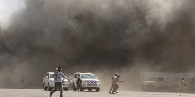 People react as dust rises after explosions hit Aden airport.