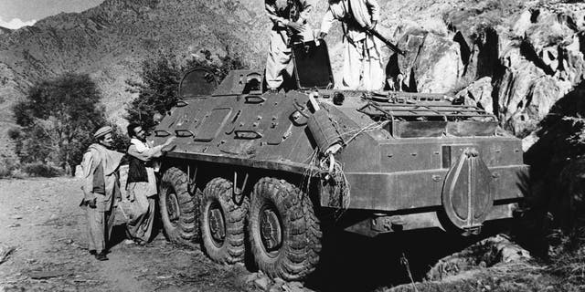 Rebel Muslim fighters inspect a Soviet tank captured in fighting with the Kabul government forces on September near Asmar, Afghanistan on Thursday, Dic. 27, 1979. The Kabul government of Hafizaullah Amin was overthrown by former Deputy Prime Minister Babrak Karmal. (AP Photo/Steve McCurry)