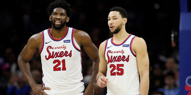 In this Dec. 13, 2019, file photo, the Philadelphia 76ers' Ben Simmons, right, and Joel Embiid talk during an NBA basketball game against the New Orleans Pelicans in Philadelphia. (AP Photo/Matt Slocum, File)