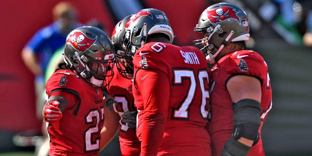 Tampa Bay Buccaneers running back Ronald Jones II (27) celebrates his score against the Minnesota Vikings with teammates, including offensive tackle Donovan Smith (76) during the first half of an NFL football game Sunday, Des. 13, 2020, in Tampa, Fla. (AP Photo/Jason Behnken)