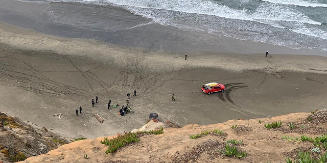Rescuers transport a woman after car plunged off a San Francisco cliff.