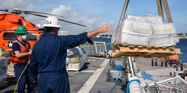 The Coast Guard Cutter James (WMSL 754) crew directs a crane operator from the flight deck offloading approximately 23,000 pounds of cocaine and 8,800 pounds of marijuana at Port Everglades, Florida, Dec. 16, 2020. The James crew patrolled the Eastern Pacific Ocean in support of enhanced counter-narcotics operations in the Western Hemisphere to disrupt transnational crime organizations. (U.S. Coast Guard photo by Petty Officer 3rd Class Jose Hernandez)