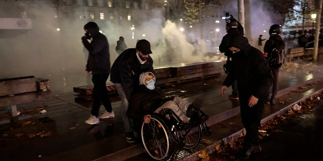 Demonstrators leave the Place de la Republique among tear gas after a demonstration, Dec. 5, in Paris. Thousands marched in protests around France on Saturday against a contested security bill with tensions quickly rising at the Paris march as intruders set fire to several cars, broke windows and tossed projectiles at police. (AP Photo/Lewis Joly)