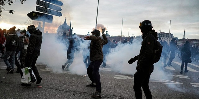 A man throws a bottle at the police during a demonstration in Lyon, central France, Dec. 5. Thousands marched in protests around France on Saturday against a contested security bill with tensions quickly rising at the Paris march as intruders set fire to several cars, broke windows and tossed objects at police. (AP Photo/Laurent Cipriani)