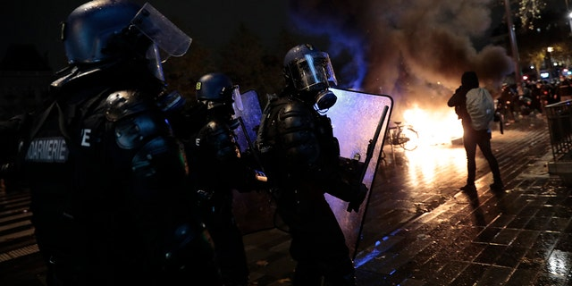 Riot police officers advance during a demonstration, Dec. 5, in Paris. Thousands marched in protests around France on Saturday against a contested security bill with tensions quickly rising at the Paris march as intruders set fire to several cars, broke windows and tossed projectiles at police. (AP Photo/Lewis Joly)