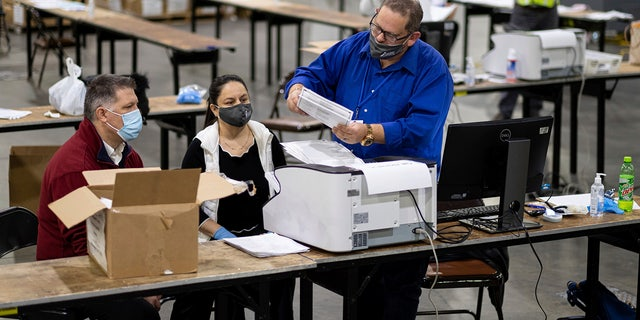 Workers scan ballots as the Fulton County presidential recount gets under way Wednesday morning, Nov. 25, 2020, at the Georgia World Congress Center in Atlanta. (AP Photo/Ben Gray)