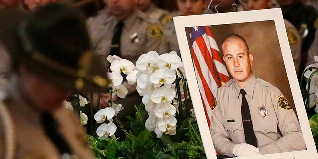A portrait sits next to the casket of Los Angeles County Sheriffs Deputy Joseph Solano during a memorial service Monday morning June 24, 2019 at Cathedral of Our Lady of the Angels in Los Angeles. (Al Seib / Los Angeles Times via Getty Images)