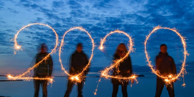 Four people write the year 2020 with sparklers into the evening sky at the stand of the Baltic Sea island of Rügen (shot with long time exposure). (Photo by Patrick Pleul/picture alliance via Getty Images)