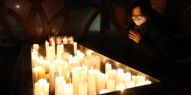 SEOUL, SOUTH KOREA - DECEMBER 31: A woman prays at the Chogey temple during the New Year Eve on December 31, 2020 in Seoul, South Korea. Seoul's city government has cancelled its annual New Year's Eve bell-ringing ceremony in the Jongno neighborhood for the first time since 1953. Normally an estimated 100,000 people would attend the ceremony, in which citizens ring a large bell in a traditional pavilion when the clock strikes midnight. Eeastern coastal areas have closed beaches and other spots where people typically gather on New Year's Day to watch the sunrise. (Photo by Chung Sung-Jun/Getty Images)