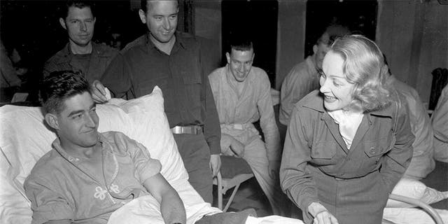 Marlene Dietrich meets a wounded soldier from Texas at a United States hospital in Belgium, November 1944.