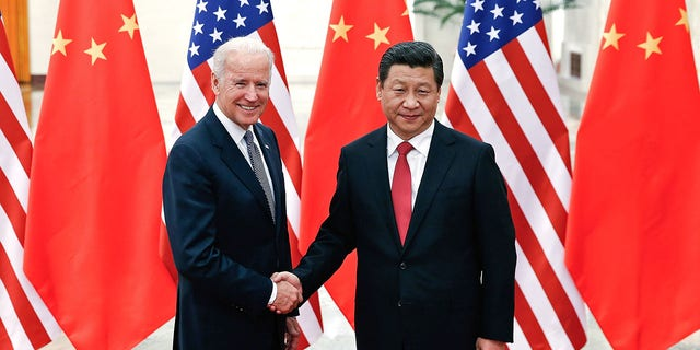 Chinese President Xi Jinping (R) shake hands with then-U.S Vice President Joe Biden (L) inside the Great Hall of the People on December 4, 2013 in Beijing, China. (Photo by Lintao Zhang/Getty Images)