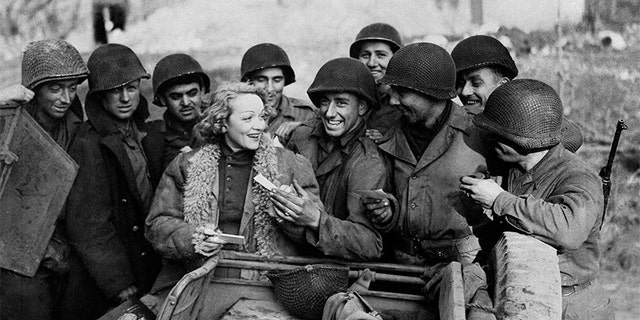 Marlène Dietrich, entertaining on the front lines, signs autographs for American soldiers, circa 1945.