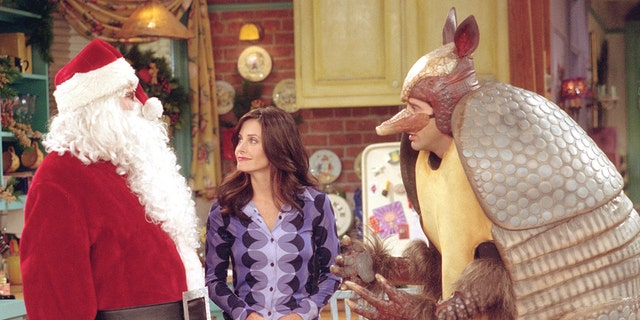 "Matthew Perry (left), Courteney Cox (center) and David Schwimmer (right) in ""Friends."" Schwimmer's Ross Gellar is dressed as the fictional Holiday Armadillo (Warner Bros. Television)"