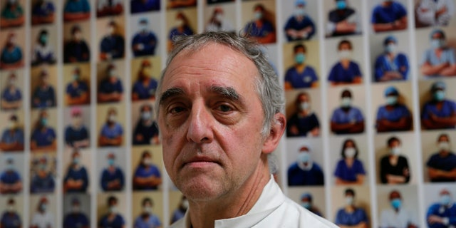 Dr. Philippe Montravers poses in front of a collection of portraits of medical staff at Bichat Hospital, AP-HP, in Paris.