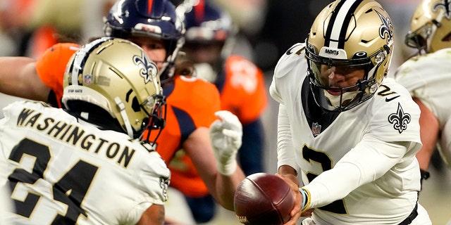 New Orleans Saints quarterback Jameis Winston (2) hands off to running back Dwayne Washington (24) during the second half of an NFL football game against the Denver Broncos, Sondag, Nov.. 29, 2020, in Denver. (AP Photo/Jack Dempsey)