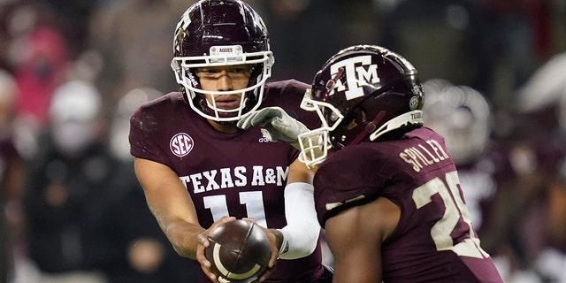 Texas A&M quarterback Kellen Mond (11) hands the ball off to running back Isaiah Spiller (28) during the fourth quarter of an NCAA college football game against LSU, Saturday, Nov. 28, 2020, in College Station, Texas. (AP Photo/Sam Craft)