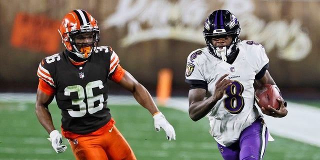 Baltimore Ravens quarterback Lamar Jackson (8) scrambles under pressure from Cleveland Browns cornerback M.J. Stewart Jr. (36) during the second half of an NFL football game, Maandag, Des. 14, 2020, in Cleveland. (AP Photo/Ron Schwane)