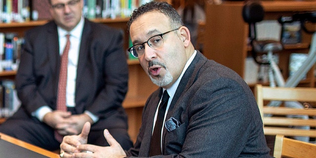 FILE - In this Jan. 28, 2020 file photo, Connecticut State Commissioner of Education Miguel Cardona speaks with Berlin High School students while on a tour of the school. (Devin Leith-Yessian/Berlin Citizen/Record-Journal via AP)