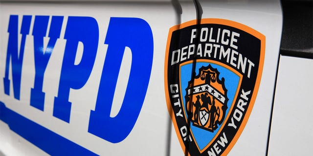 NYPD sign with logo on police patrol car in New York City.