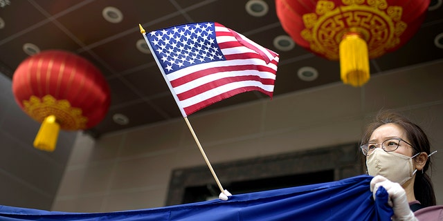A protester holds a U.S. flag outside the Chinese consulate in Houston, July 24, 2020, after the U.S. State Department ordered China to close the consulate. (Getty Images)