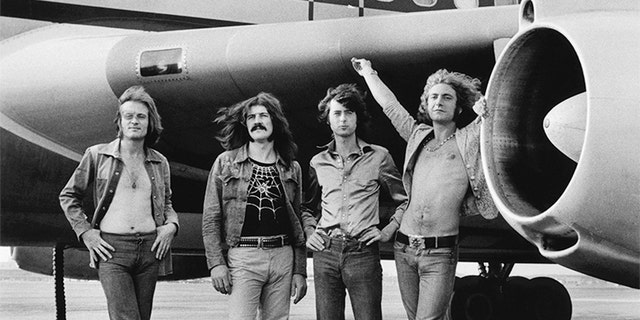 (L-R) John Paul Jones, John Bonham, Jimmy Page and Robert Plant of Led Zeppelin in front of a plane in NY. July 24, 1973.