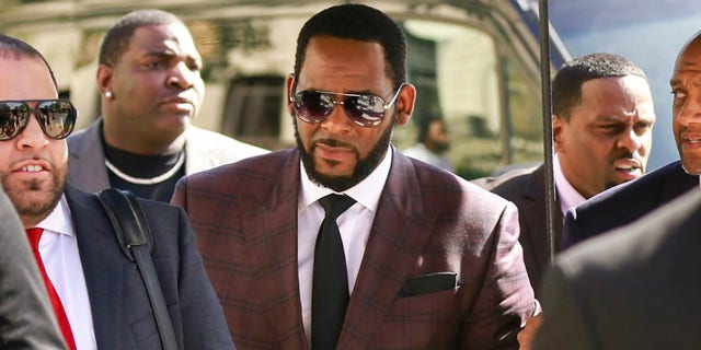In this June 26, 2019 file photo, R&B singer R. Kelly, center, arrives at the Leighton Criminal Court building for an arraignment on sex-related felonies in Chicago.