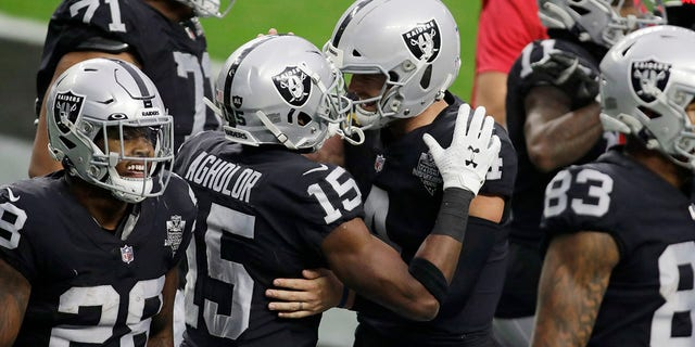 Las Vegas Raiders quarterback Derek Carr, regs in die middel, embraces wide receiver Nelson Agholor (15) after Agholor made a touchdown catch against the Indianapolis Colts during the first half of an NFL football game, Sondag, Des. 13, 2020, in Las Vegas. (AP Photo/Isaac Brekken)