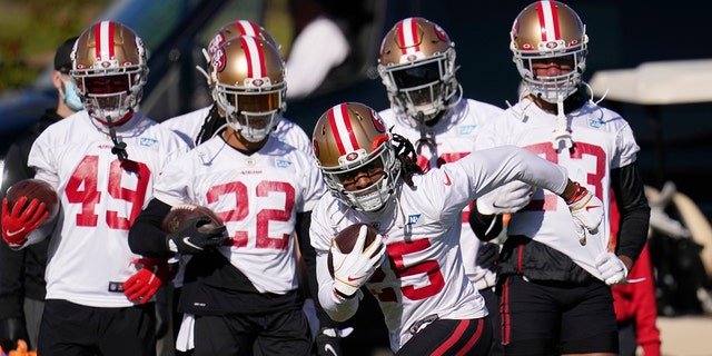 San Francisco 49ers cornerback Richard Sherman takes off with the ball during NFL football practice near State Farm Stadium, home of the Arizona Cardinals, Thursday, Dec. 3, 2020, in Glendale, Ariz. The 49ers are on a three-week road trip after being forced from their stadium and practice facility because of strict new COVID-19 protocols in their home county in Northern California. (AP Photo/Ross D. Franklin)