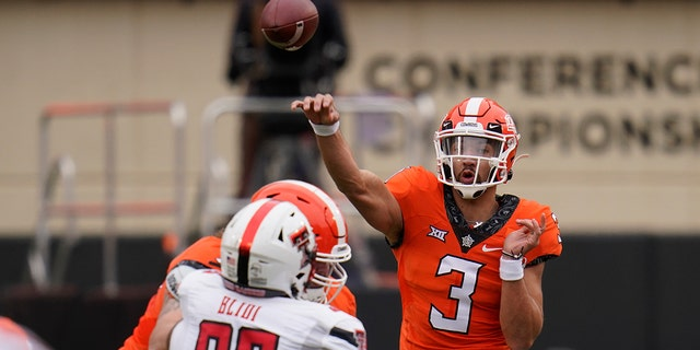 Oklahoma State quarterback Spencer Sanders (3) throws under pressure from Texas Tech defensive lineman Philip Blidi (96) in the first half of an NCAA college football game in Stillwater, Okla., Saturday, Nov. 28, 2020. (AP Photo/Sue Ogrocki)
