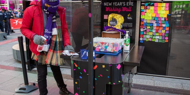 A worker in Times Square sanitizes the booth where people can write their new year wish on confetti that will shower the Crossroads of the World on New Year's Eve.
