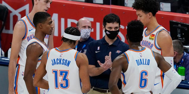 Oklahoma City Thunder head coach Mark Daigneault, center, talks with his players in the first half of a preseason NBA basketball game against the Chicago Bulls Wednesday, Dec. 16, 2020, in Oklahoma City. (AP Photo/Sue Ogrocki)