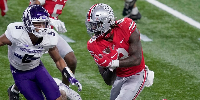 Ohio State running back Trey Sermon, right, scores past Northwestern defensive back JR Pace (5) during the second half of the Big Ten championship NCAA college football game, Saturday, Dec. 19, 2020, in Indianapolis. (AP Photo/Darron Cummings)